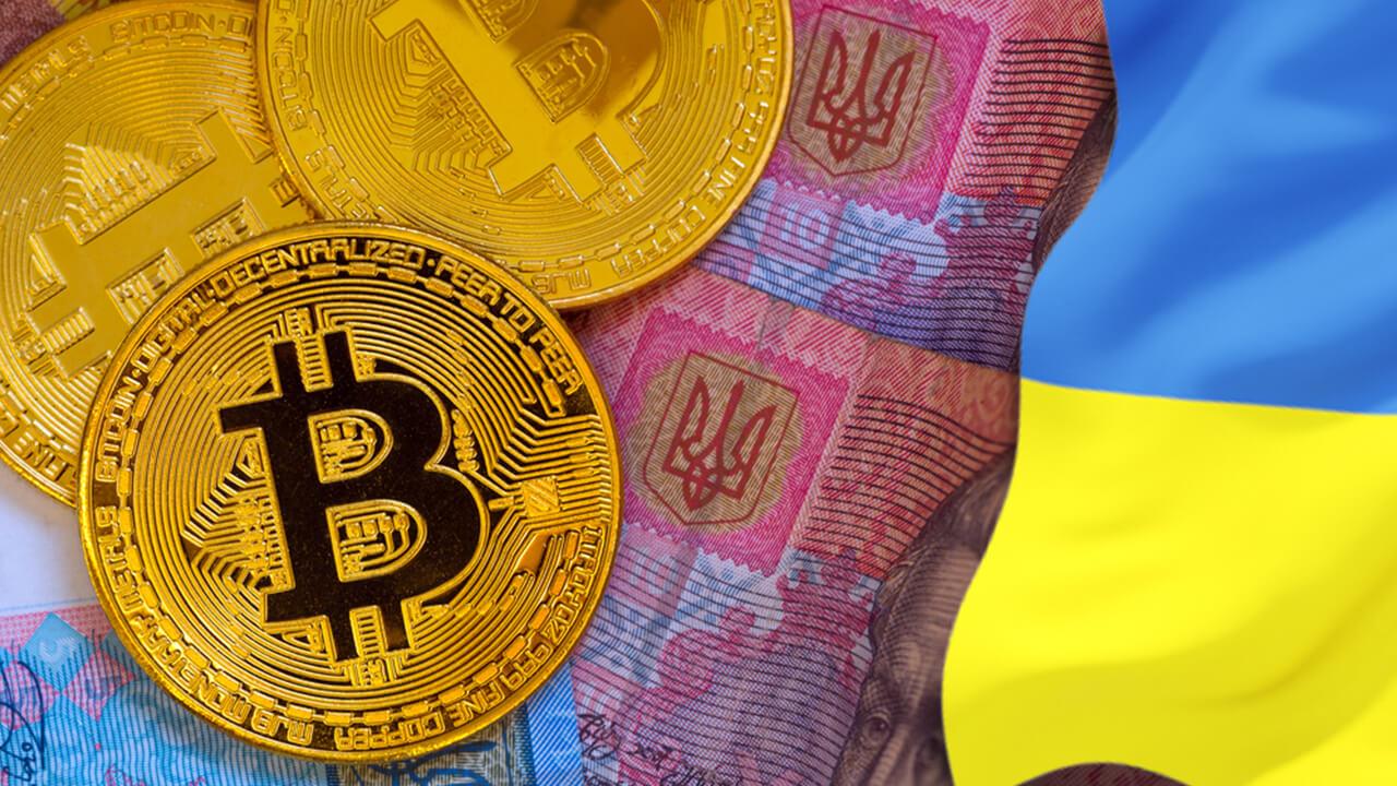 монета биткоина на фоне флага Украины и украинской гривны